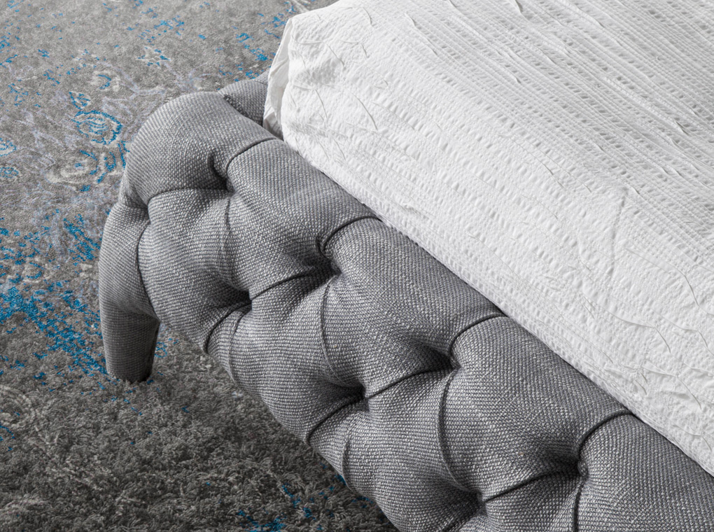 Bed upholstered in tufted fabric