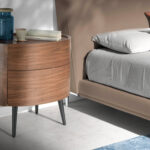 Oval bedside table in walnut-colored wood and black legs