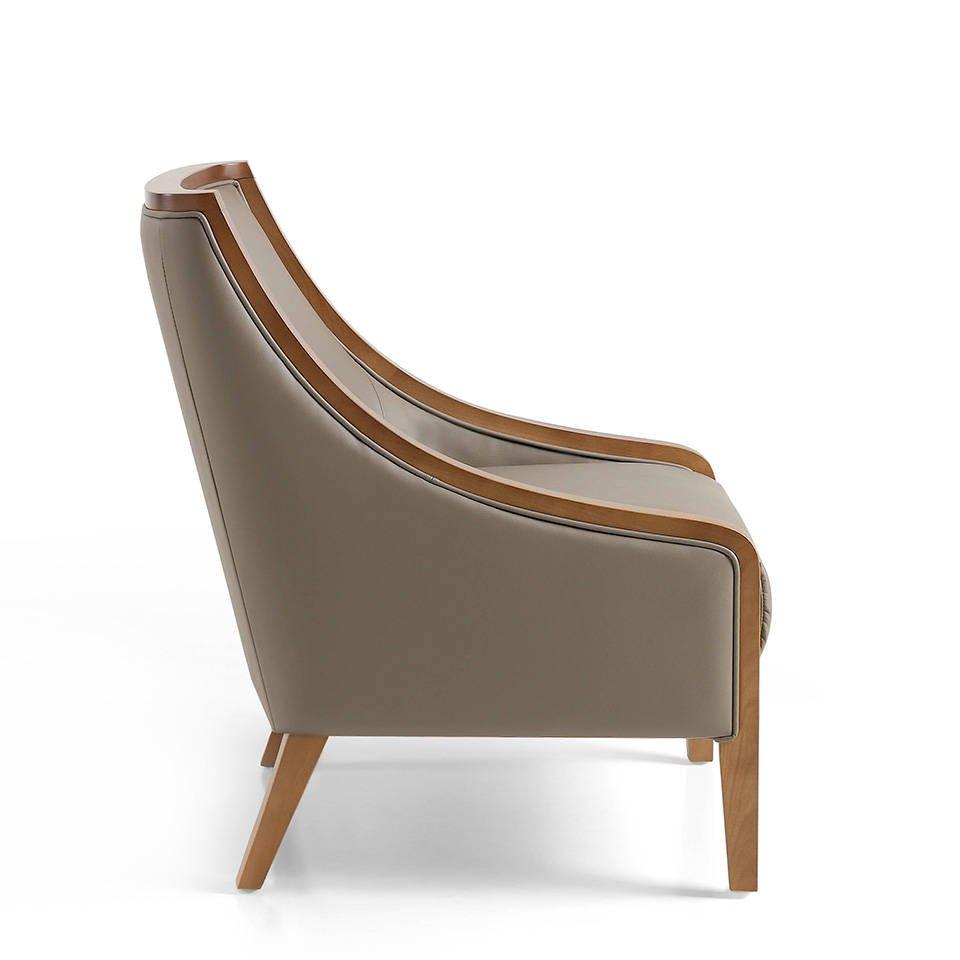 Sillón tapizado en piel con patas madera en color Nogal