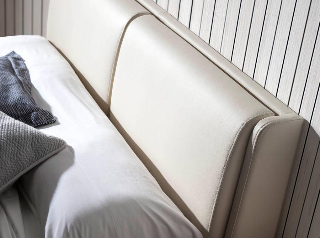 Cama fabricada en chapa de roble con cabecero tapizado