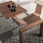 Extendable solid wood table with walnut wood veneer with two foldable extensions.