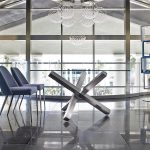 Dining table with polished stainless steel base.