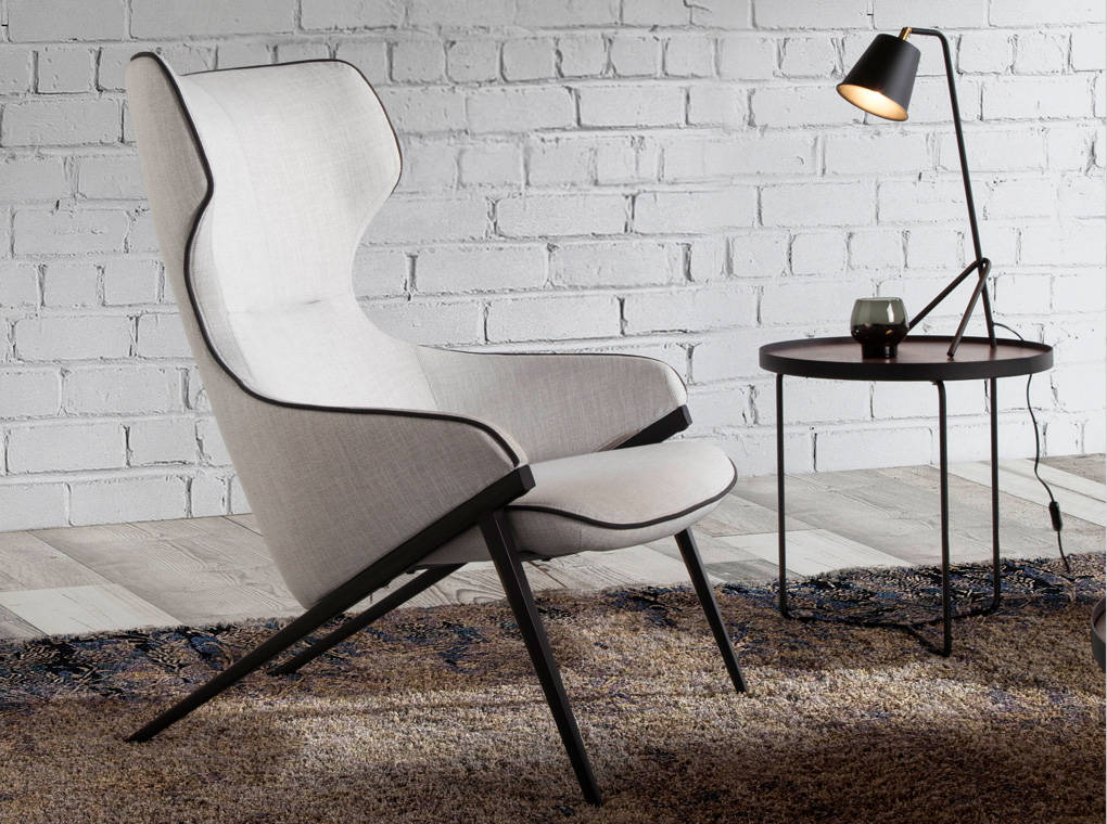 Armchair upholstered in fabric with black steel trim and legs